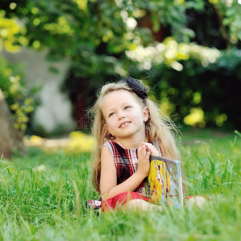有一本书的逗人喜爱的小女孩在夏天公园 图库摄影