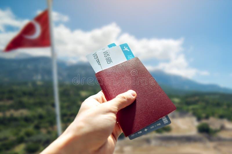 有一本护照和两机票在土耳其风景背景的手  旅行和假期在美好的地方 免版税库存照片