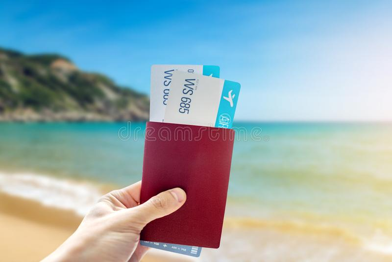 有一本护照和两机票在海的蓝色背景的手 旅行和假期在异乎寻常的地方 免版税库存照片