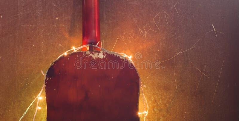 有一本诗歌选的老声学吉他在难看的东西背景, 库存图片