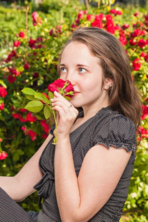 有一朵玫瑰的女孩在庭院里 免版税库存图片