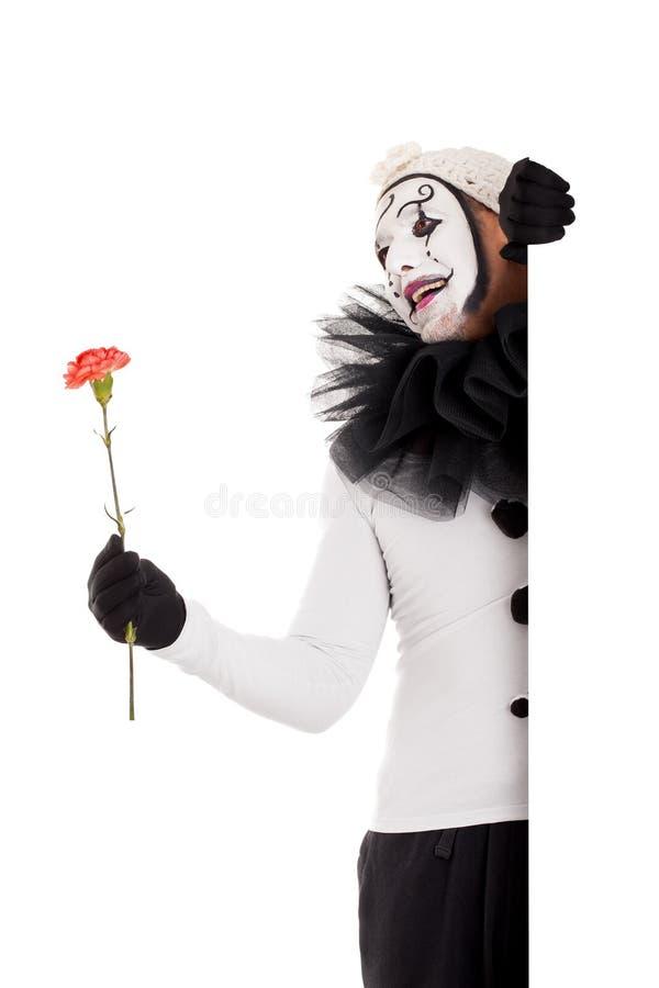 有一朵花的一个男性小丑在手 免版税库存照片