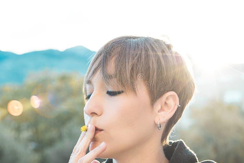 有一朵花的俏丽的妇女在她的嘴 抽花,健康概念的女孩 库存照片