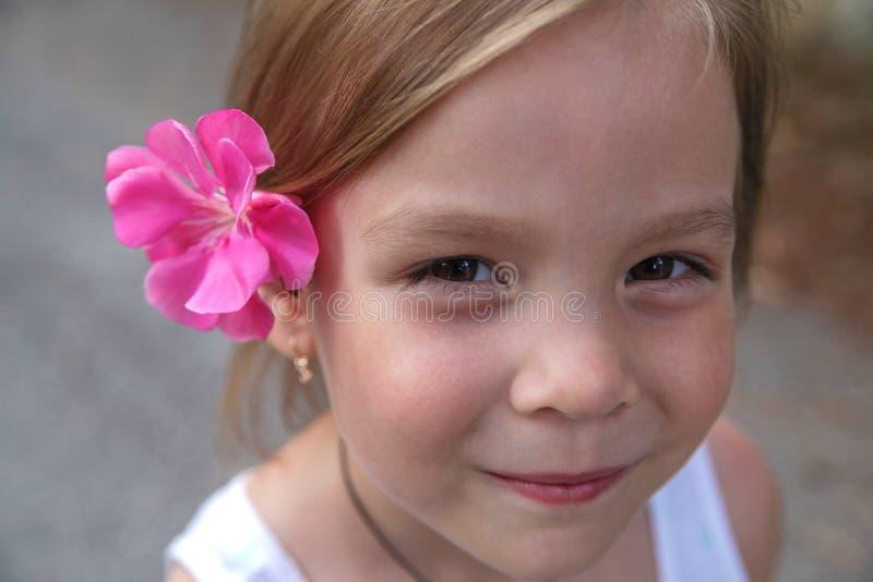 有一朵花的小女孩在她的头发 免版税库存图片