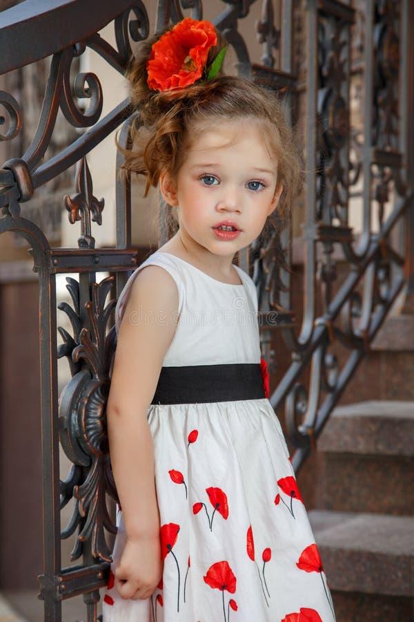 有一朵花的美丽的小女孩在她的头发 库存图片