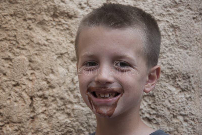 有一杂乱面孔微笑的年轻男孩愉快 图库摄影