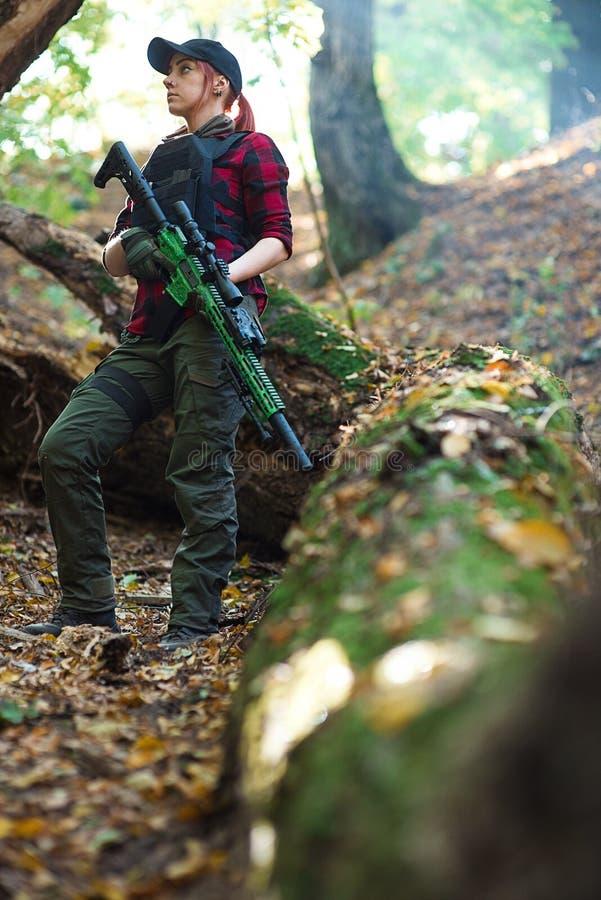 有一杆枪的战士女孩在森林里 图库摄影
