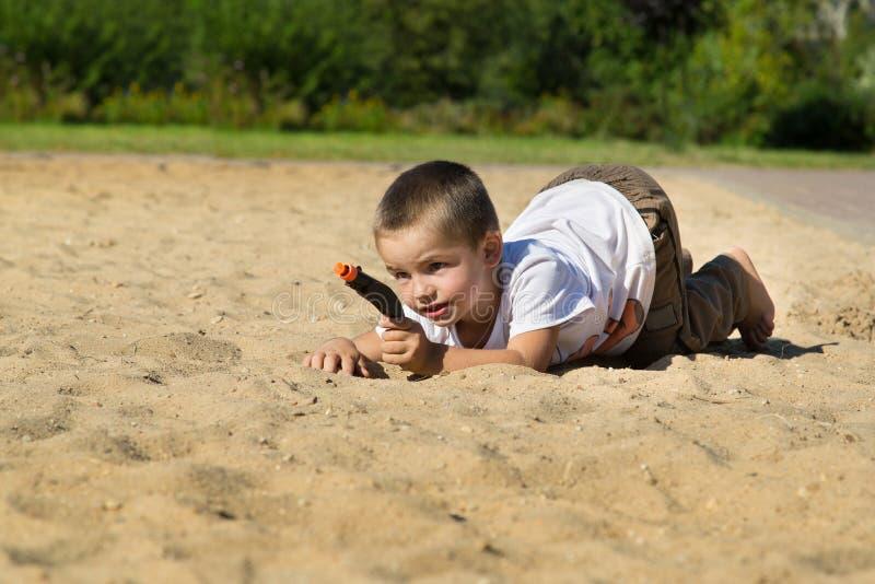 有一杆枪的男孩在操场 免版税库存图片