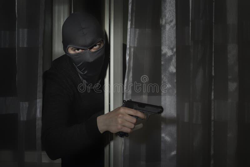 有一杆枪的窃贼在他的手上和在有一个裂缝的一个帽子眼睛告密者的到房子里通过门在晚上 图库摄影