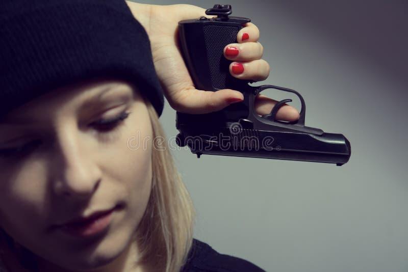 有一杆枪的年轻绝望妇女在他的手上 库存图片