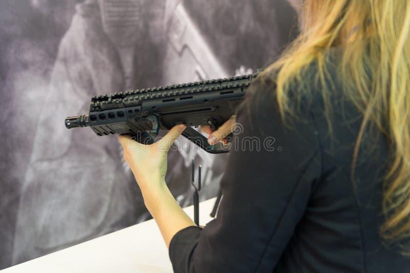 有一杆自动步枪的女孩在柜台的手上 武器 库存图片