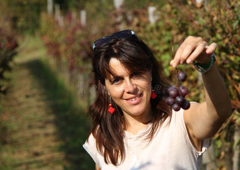 有一束小的葡萄的美丽的妇女在秋天 库存图片