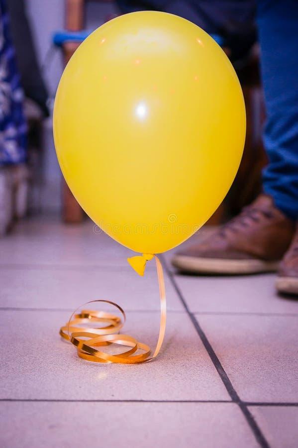 有一条丝带的偏僻的气球在地板上,当党结束 免版税库存图片