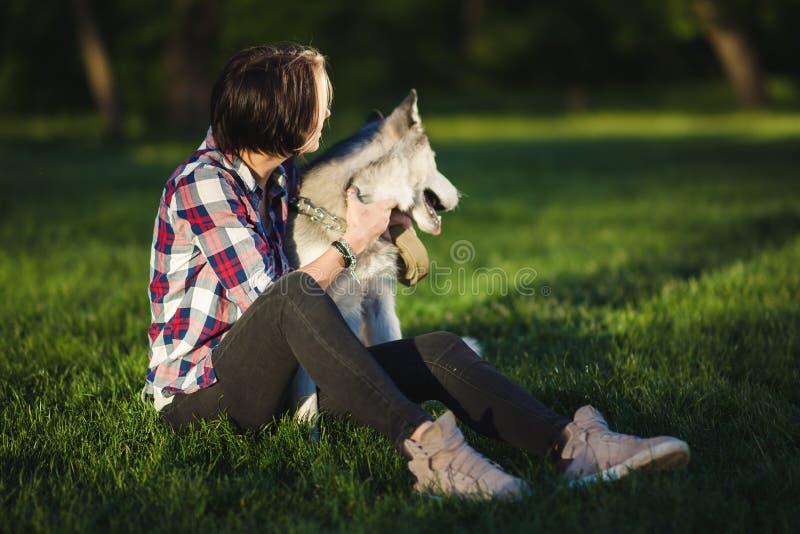 有一条多壳的狗的美丽的少妇 免版税图库摄影