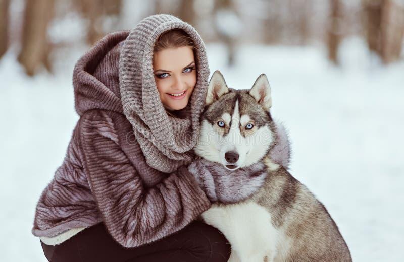有一条多壳的狗的逗人喜爱的女孩在冬天森林背景中, clos 图库摄影