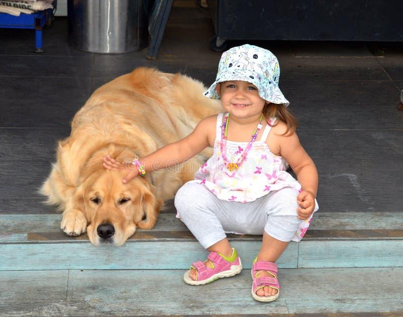 有一条大狗的愉快的女婴 库存图片