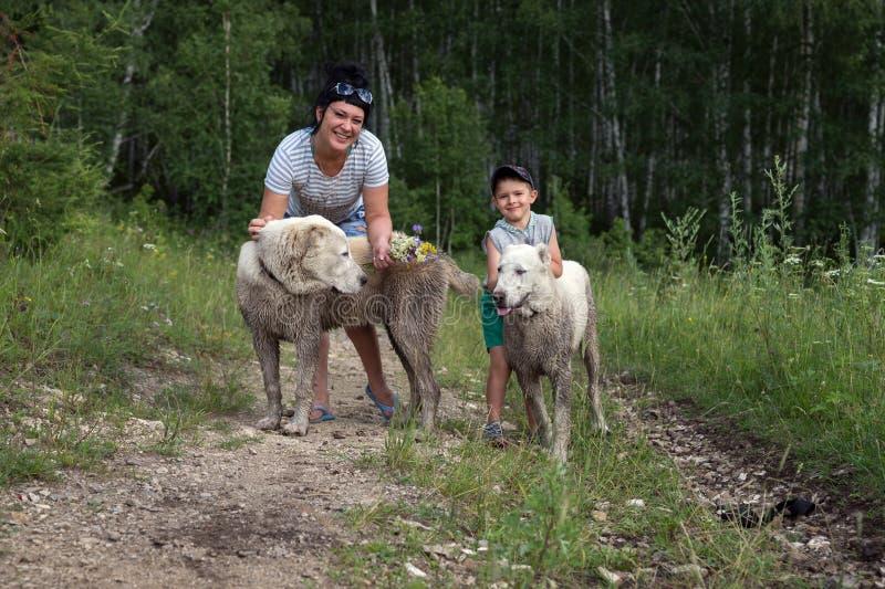 有一条小男孩和大白色狗的一名愉快的妇女在一条森林公路站立,在夏天 免版税库存图片