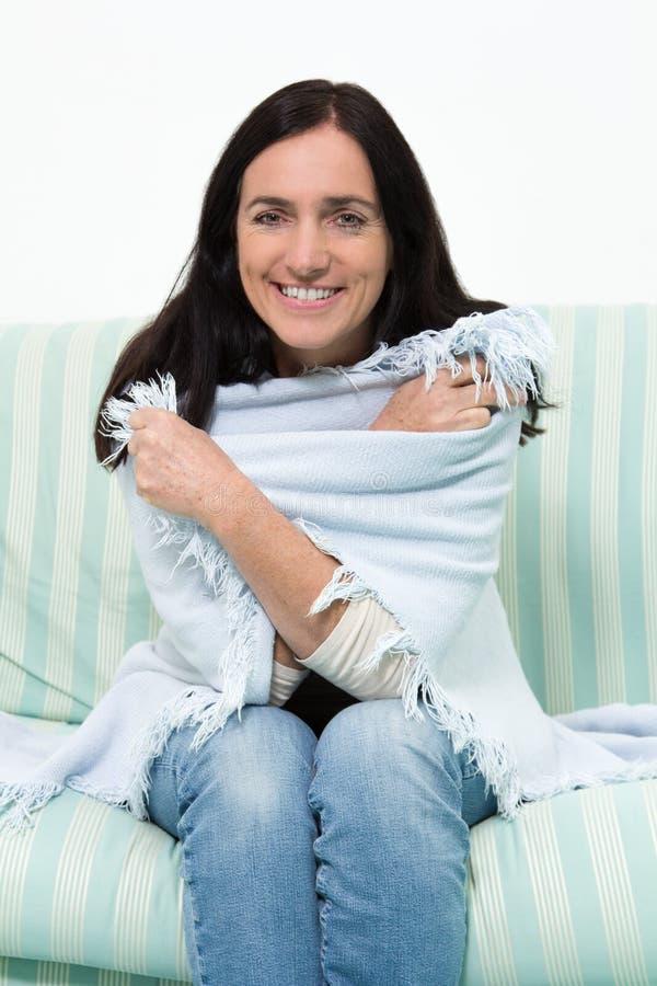 有一条毯子的妇女在长沙发 免版税库存照片