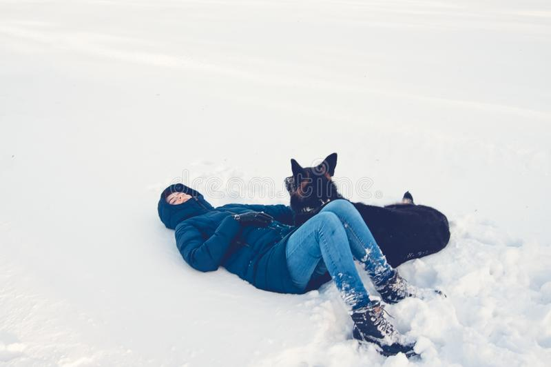 有一条狗的女孩在冬天湖的岸 库存照片