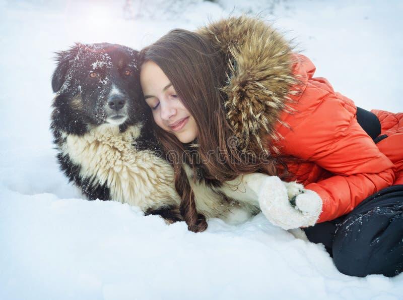 有一条狗的女孩在雪 免版税图库摄影