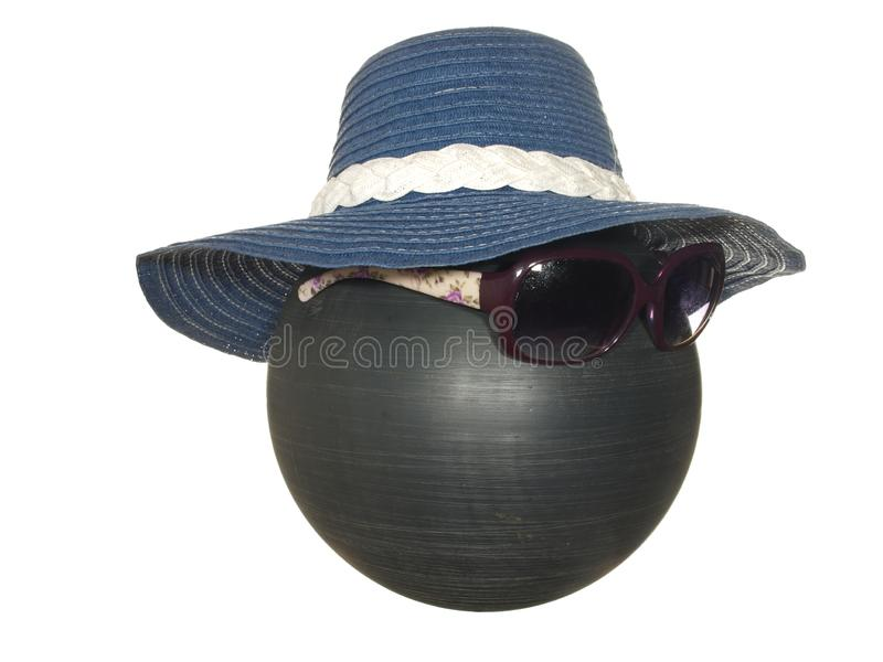 有一条白色丝带的夫人的蓝色帽子和在白色背景隔绝的一个黑塑料球的黑暗的风镜 库存图片