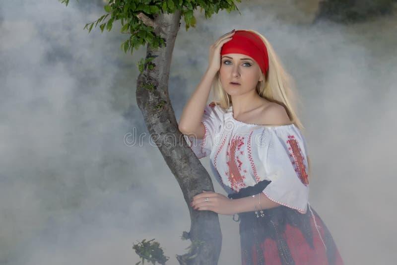 有一条红色围巾、一件传统罗马尼亚女衬衫和一条红色和黑裙子的美丽的年轻白肤金发的女孩 免版税库存照片