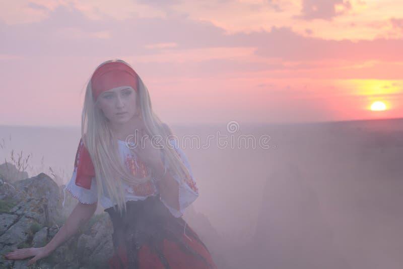 有一条红色围巾、一件传统罗马尼亚女衬衫和一条红色和黑裙子的美丽的年轻白肤金发的女孩 免版税库存图片