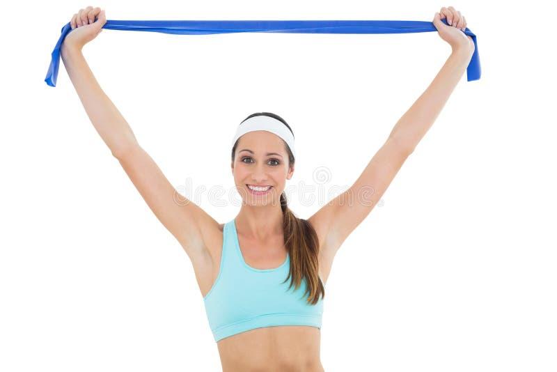 有一条蓝色瑜伽传送带的微笑的适合的少妇 库存照片