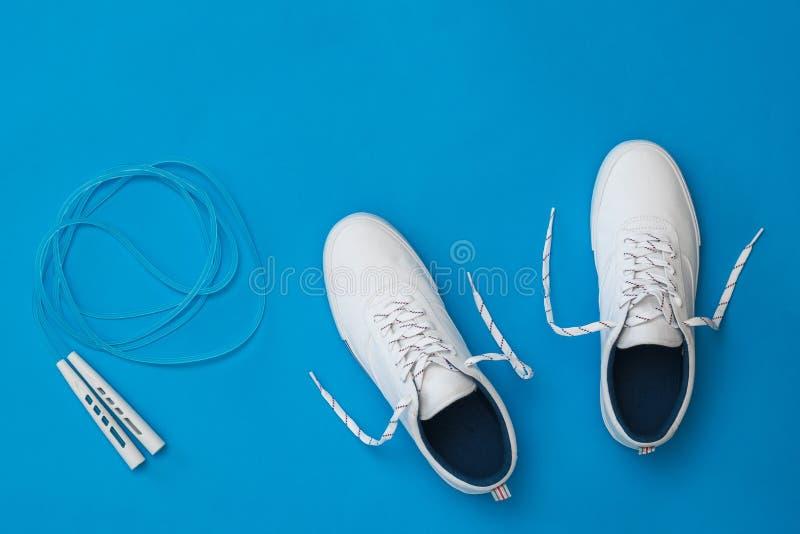 有一条蓝色跳绳的白色运动鞋在蓝色背景 体育样式 r 免版税图库摄影