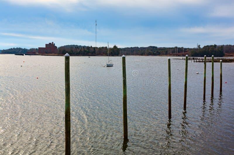 有一条风船的老木打桩在距离 免版税库存照片
