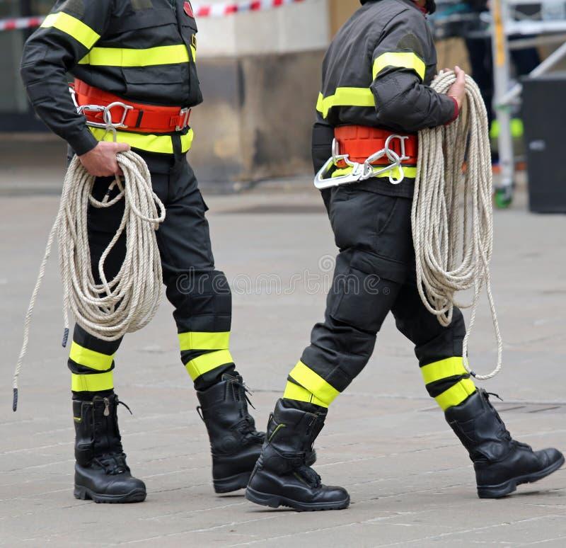 有一条绳索的两名消防队员在救援活动时 免版税图库摄影