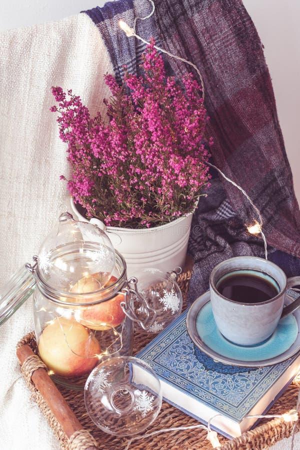 有一杯咖啡的一个盘子、苹果在瓶子,轻链、花和围巾 库存图片