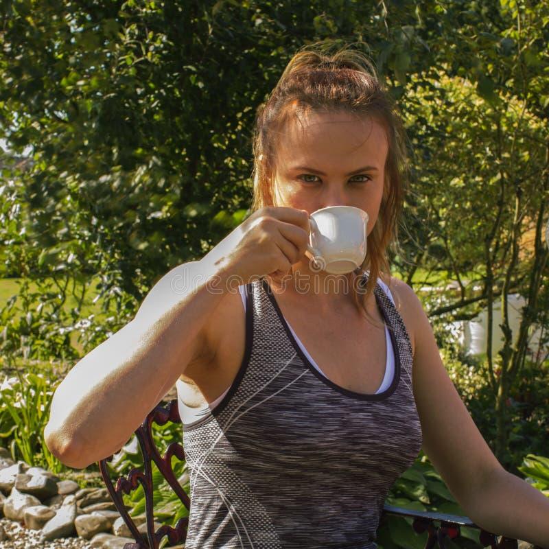 有一杯咖啡的一名年轻运动的妇女,晴天,公园 库存照片