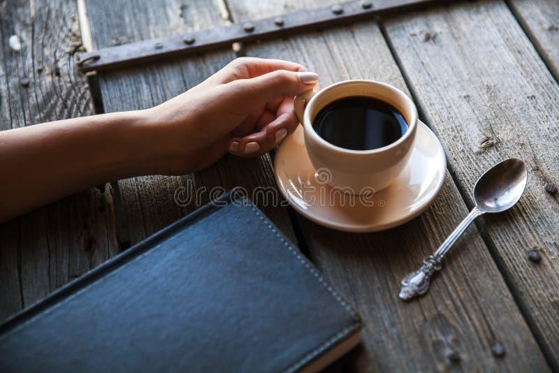有一杯咖啡的女性手,采取笔记 它运作纪录 事务 库存图片