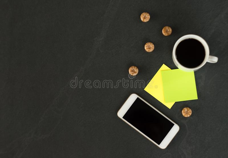 有一杯咖啡的白色电话,笔记的多彩多姿的贴纸和甜点在一张黑桌上 免版税库存照片
