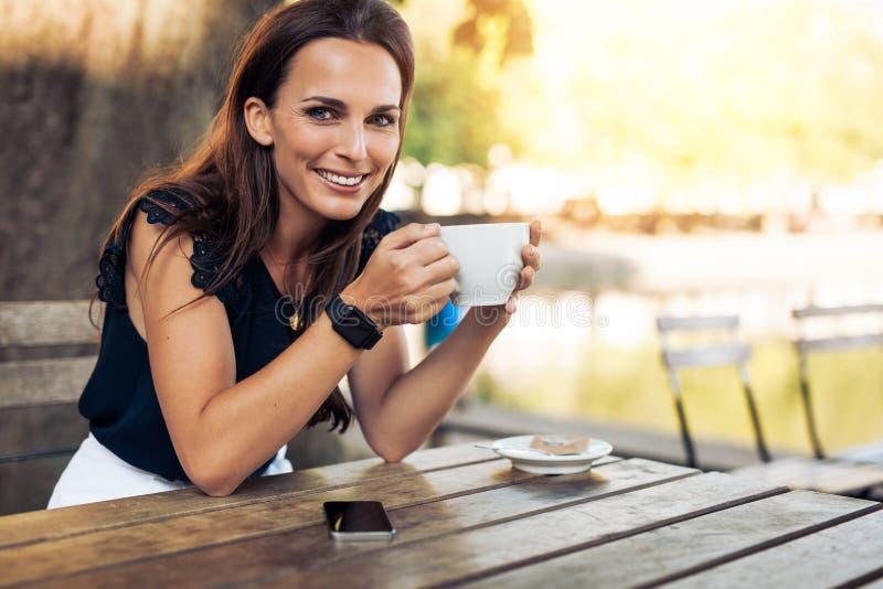 有一杯咖啡的美丽的少妇 免版税库存照片