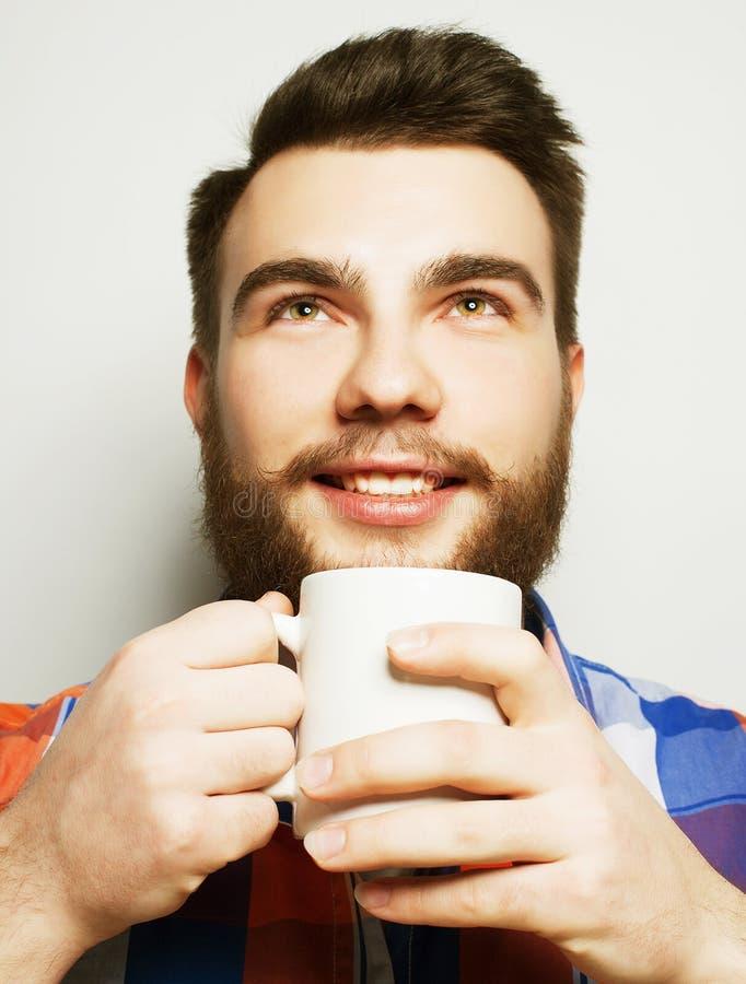 有一杯咖啡的年轻有胡子的人 免版税图库摄影