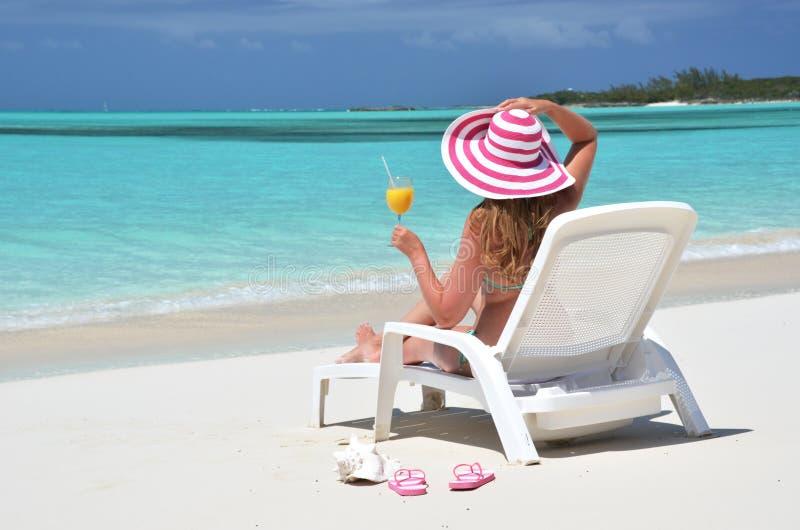 有一杯的女孩在海滩的橙汁 免版税库存照片