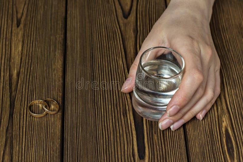有一杯的女性手酒精,特写镜头,木背景,拷贝空间 免版税库存图片