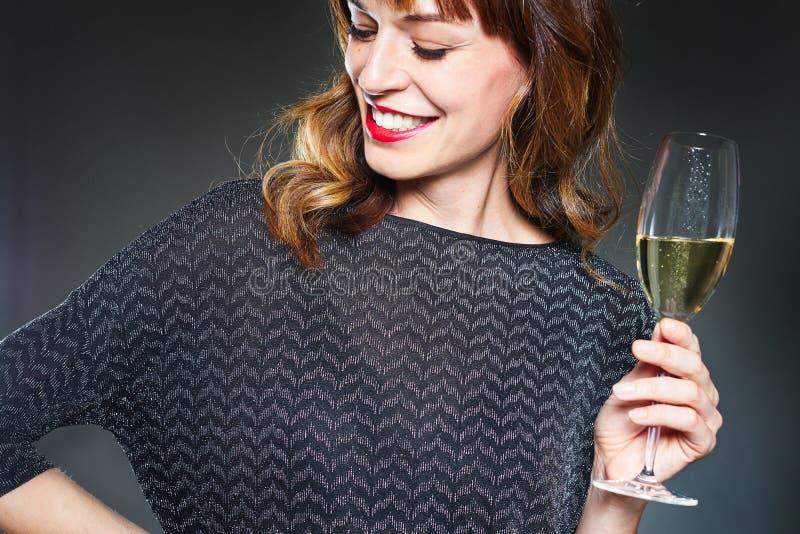 有一杯的妇女在黑暗的背景的香槟 有长的卷发和完善的牙的微笑的夫人庆祝和 库存图片