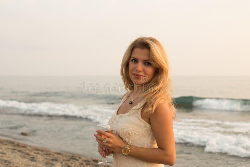 有一杯的美丽的白肤金发的夫人由海边的桃红葡萄酒 免版税库存照片