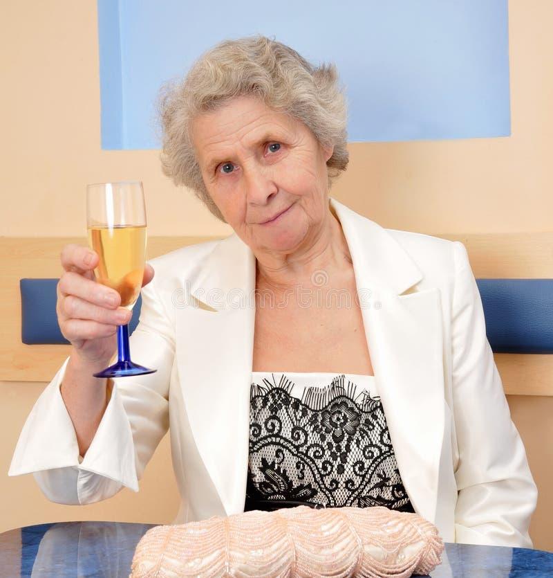 有一杯的资深妇女酒 免版税库存照片