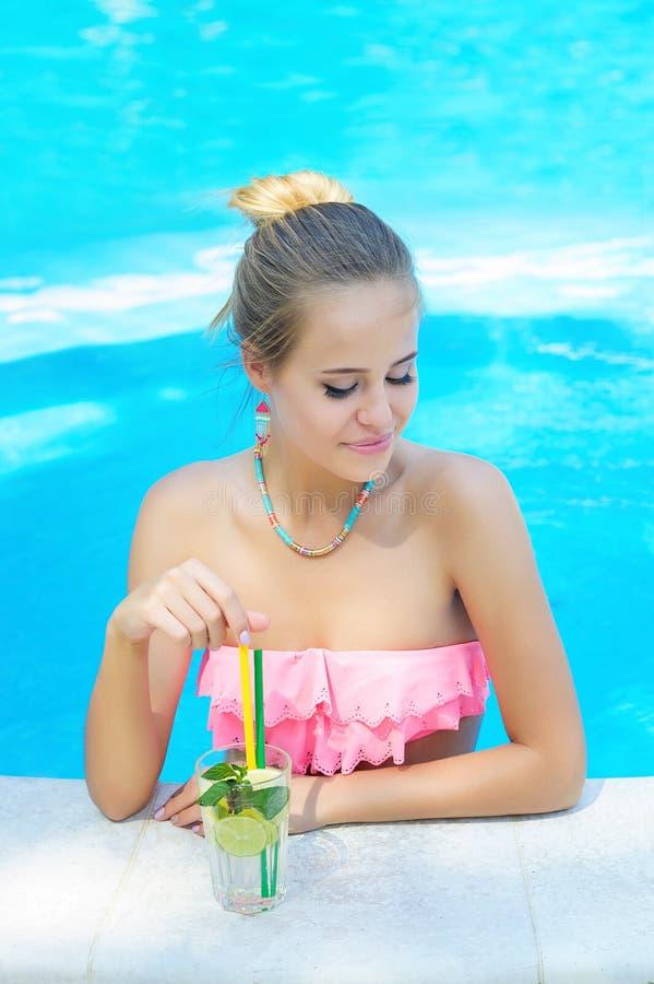有一杯的年轻时髦白肤金发的妇女刷新的柠檬水 免版税库存图片