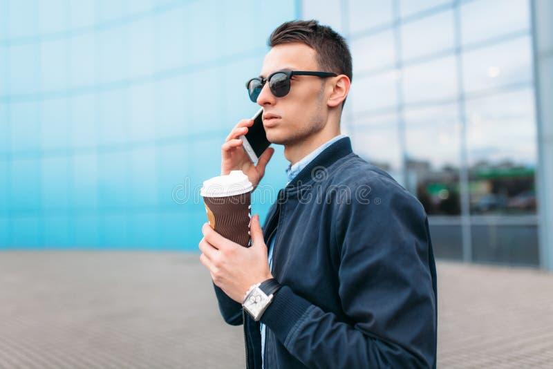 有一杯纸咖啡的一个人,审阅城市、一个英俊的人时髦的衣裳的和太阳镜,打电话 免版税库存图片