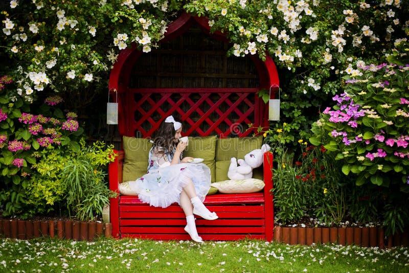 有一杯茶的女孩在庭院里 免版税库存图片