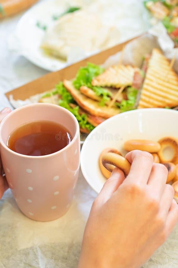 有一杯茶的女性手和百吉卷 免版税库存图片