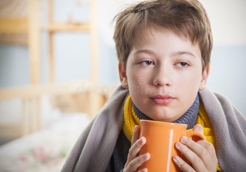 有一杯茶的病的男孩在家 库存照片