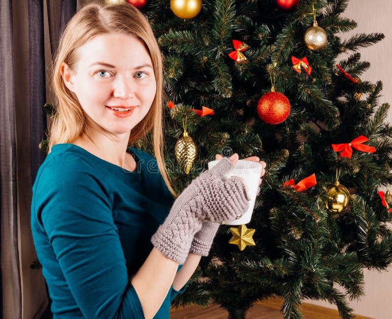 有一杯茶的美丽的女孩在圣诞树附近的 免版税库存照片