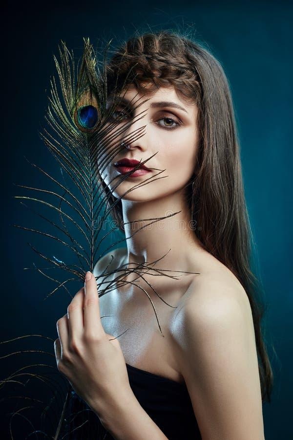 有一根孔雀羽毛的阿拉伯东部妇女在她的在她的面孔附近的手上 秀丽时尚构成阿拉伯妇女,大美丽的眼睛 图库摄影