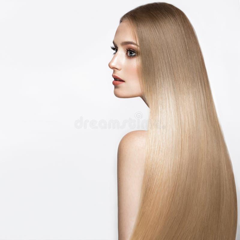 有一根完全光滑的头发的美丽的白肤金发的女孩和经典构成 秀丽表面 免版税图库摄影